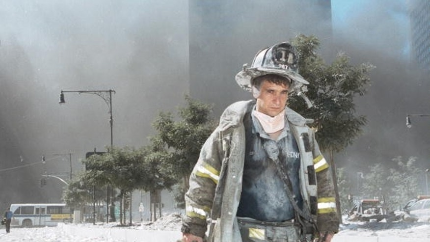 An unidentified New York City firefighter walks away from Ground Zero after the collapse of the Twin Towers September 11, 2001 in New York City.