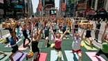 "NEW YORK - JUNE 21:  Yoga enthusiasts from across the country participate in the annual ""Summer Solstice in Times Square Yoga-thon"" as taxis drive past June 21, 2007 in New York City. The summer solstice is the first official day of summer and the longest day of the year.  (Photo by Mario Tama/Getty Images)"