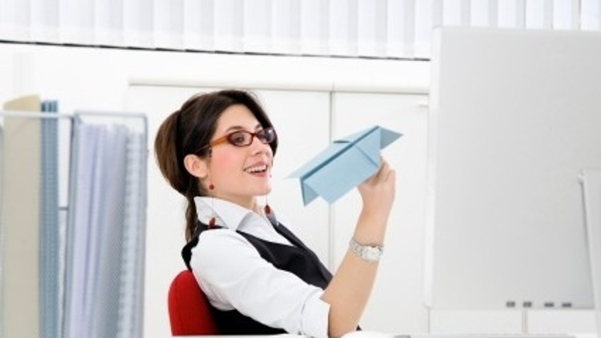 Young businesswoman throwing paper airplane in office