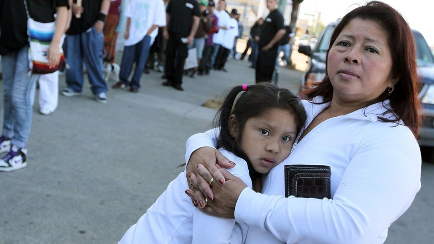 A woman embraces her child in Oakland, California.  (Photo by Justin Sullivan/Getty Images)