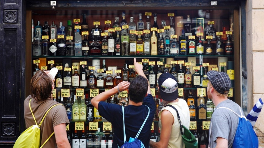 Men look at a window display of alcoholic drinks at a shop in central Barcelona July 31, 2012. Capital flight from Spain gathered pace in May and the central government deficit rose further above target in June, taking the country two steps closer to the full-scale bailout it is desperate to avoid.  REUTERS/Albert Gea (SPAIN - Tags: BUSINESS) - RTR35RCO