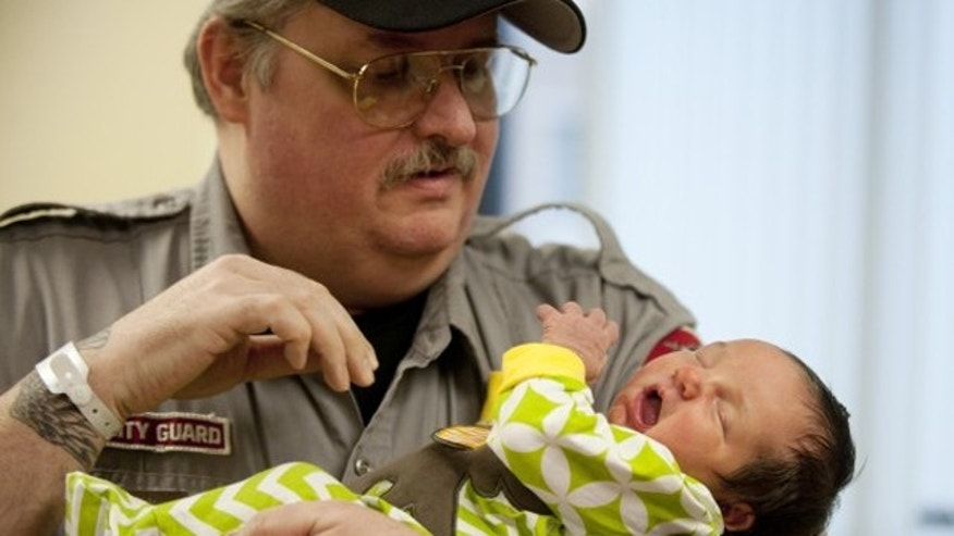 Feb. 12, 2013: Mike Ackley, a security guard at the Jackson County Courthouse holds his new daughter, Kimberly.