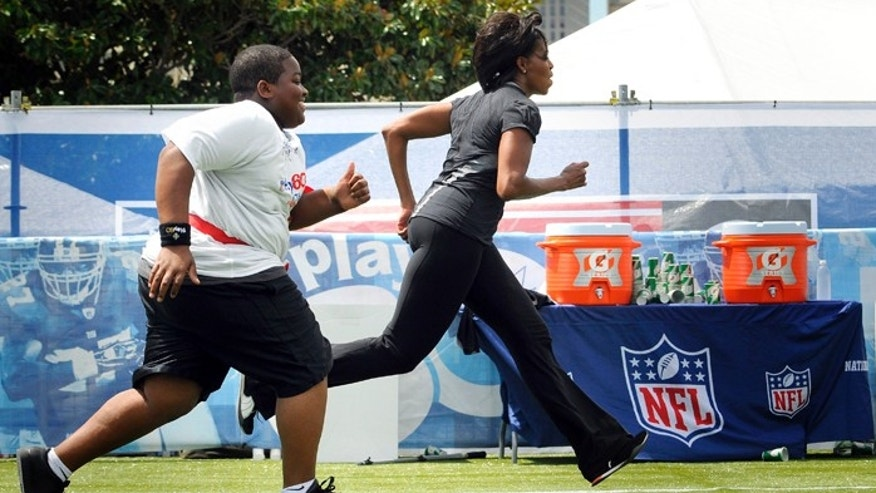 "U.S. first lady Michelle Obama plays flag football with children, former NFL players and coaches during her ""Let's Move"" campaign to fight childhood obesity."