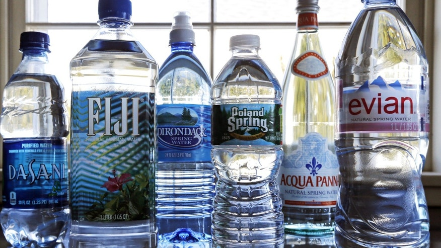 In this Tuesday, March 5, 2013 photo, a selection of bottled waters stands on a kitchen counter in East Derry, N.H. Soda's reign as America's most popular drink could be entering its twilight years, with plain old bottled water making a run for the top spot. (AP Photo/Charles Krupa)