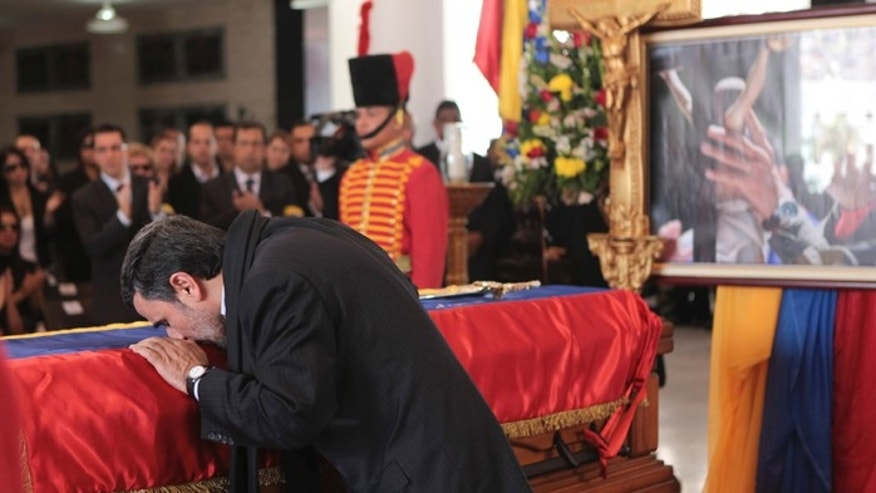 Iran's President Mahmoud Ahmadinejad pays tribute to late Venezuelan President Hugo Chavez, during the funeral service at the Military Academy in Caracas March 8, 2013.