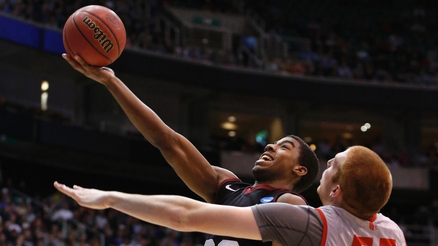 Harvard guard Wesley Saunders (23) takes a shot while defended by New Mexico center Alex Kirk (53) during the second half of their second round NCAA tournament basketball game in Salt Lake City, Utah.