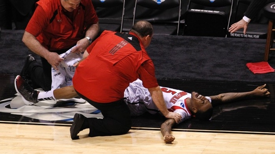 Louisville Cardinals guard Kevin Ware (5) is attended to by medical staff after breaking his leg in the first half against the Duke Blue Devils during their Midwest Regional NCAA men's basketball game.