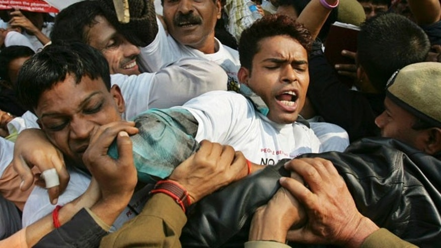 FILE: Indian police officers block demonstrators protesting against drug manufacturer Novartis' case against Indian government on drug patents in New Delhi, India.