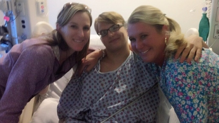 Jackson in the hospital with Carin Wilkes (L), his health teacher, and Rebecca Slade, the school nurse.  Both Wilkes and Slade will be honored by the Cobb County School Board for their quick thinking during Jackson's stroke.