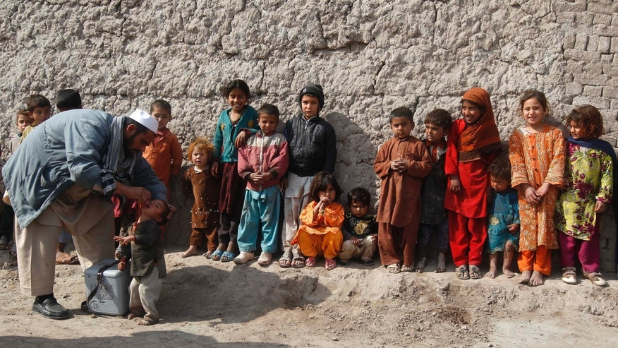 A child receives polio vaccination drops as others stand in a line during an anti-polio campaign on the outskirts of Jalalabad.