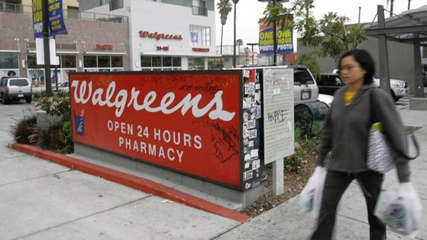 A woman walks by a Walgreen drugstore in the Hollywood selection of Los Angeles.