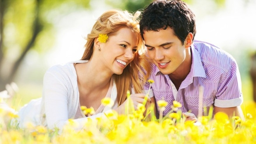 Cheerful young couple are lying among the dandelions and enjoying in the nature. 