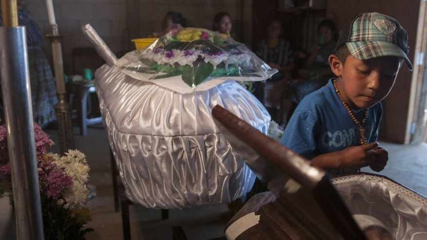Daniel Rac, 5, looks into the coffin of his friend Carlos Enrique Rac, 12, who died by food poisoning in Santo Domingo Xenacoj, west of Guatemala City, Thursday, April 11, 2013.  Four people, including two children, died and 96 others were hospitalized for food poisoning after the victims ate fruit & vegetables that weren't properly cleaned in the town of Santo Domingo Xenacoj, said the fire department.  A doctor at one of the hospitals said the medical exams show the deaths were caused by E. coli bacteria. (AP Photo/Luis Soto)