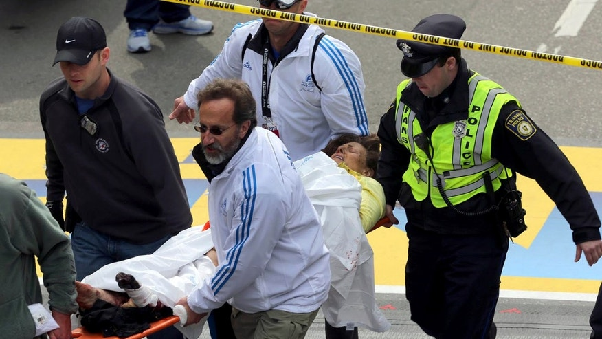 Dr. Martin Levine (bottom center in white) helps aid injured people at the finish line of the 2013 Boston Marathon following an explosion in Boston, Monday, April 15, 2013.