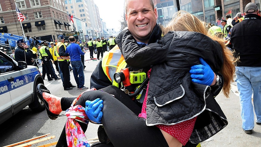 Boston Firefighter James Plourde carries an injured girl away from the scene after a bombing near the finish line of the Boston Marathon in Boston.  (AP Photo/MetroWest Daily News, Ken McGagh, File)