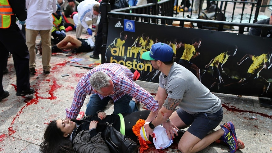 In this April 15, 2013 file photo, an injured woman is tended to at the finish line of the Boston Marathon after two bombs exploded, in Boston. As people lay badly bleeding in the smoke of the Boston Marathon bombings, rescuers immediately turned to a millennia-old medical device to save their lives -- the tourniquet.