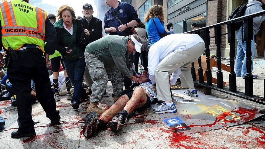 An injured person is helped on the sidewalk near the Boston Marathon finish line following an explosion in Boston, Monday, April 15, 2013.