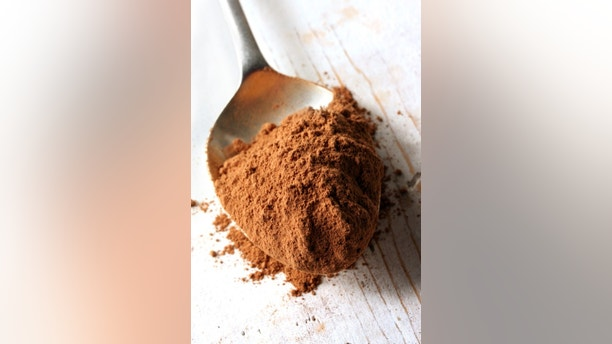 Cocoa powder on an old silver spoon, on rough wooden surface.