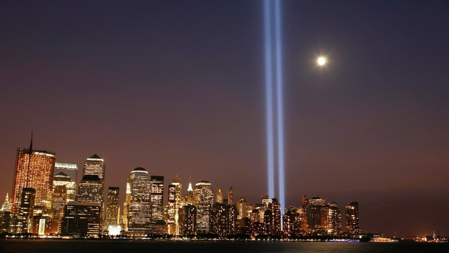 "The moon rises over lower Manhattan as the ""Tribute in Lights"" illuminates the sky."
