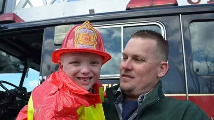 Teagan O'Grady, with his father, Ryan, as an honorary firefighter for a day. Photo by KESHIA CLUKEY via Observer-Dispatch