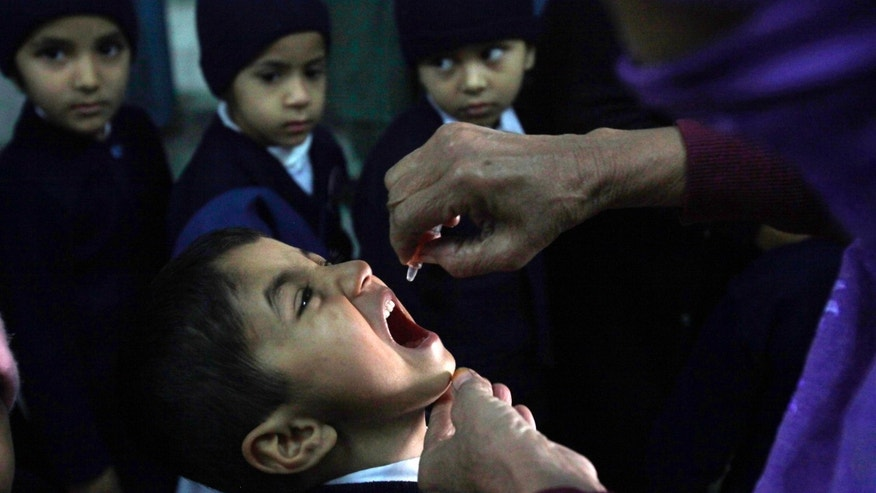 A female polio worker gives polio vaccine drops to a child in Lahore, Pakistan.