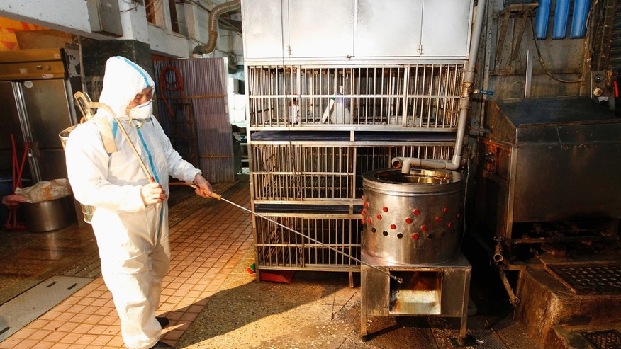A janitor sprays disinfectant at empty chicken cages in a traditional market in New Taipei city April 29, 2013.