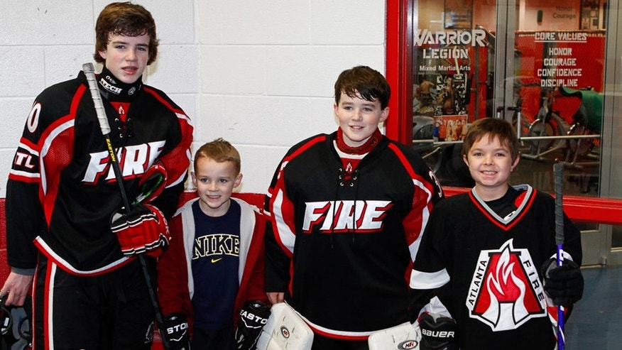 Connor (2nd from Right) and Reece (far Right) pose with Atlanta Fire teammates