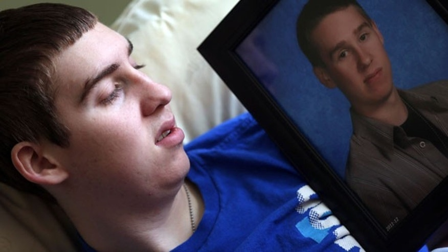 Daniel Theiss, 18, holding a photo in Mason, Ohio, of his twin brother Forrest, who was in a Cleveland hospital. The twins suffer from a genetic condition, so rare it doesn't even have a name, that affects the blood vessels in their bodies and makes them more prone to ripping and shredding.