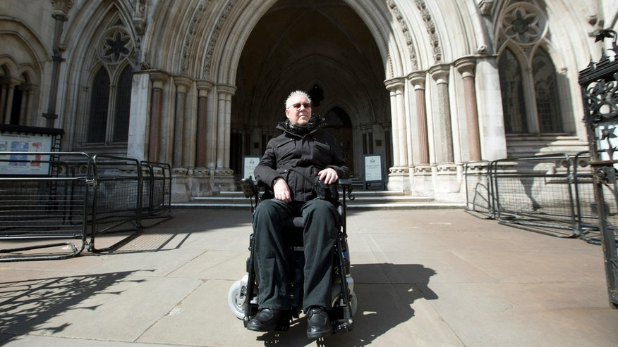 Pro-euthanasia campaigner Paul Lamb poses for photographs as he leaves the High Court in London.