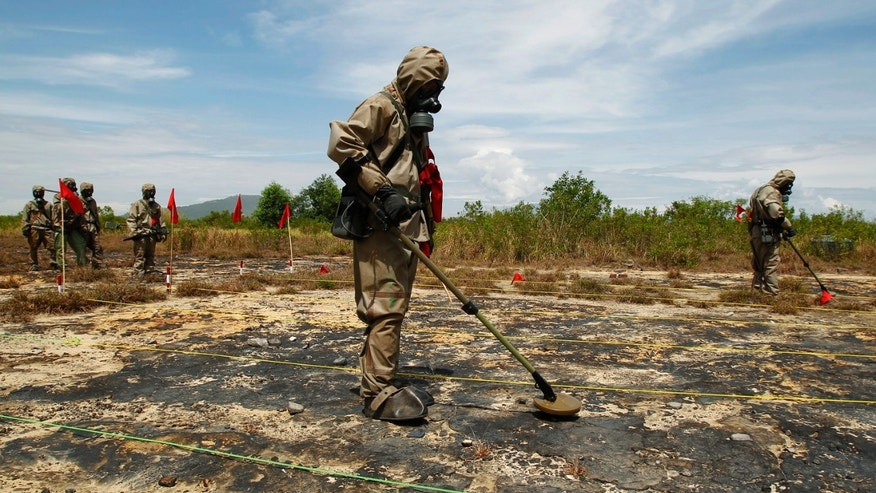 "Soldiers detect Unexploded Ordnance (UXO) and defoliant Agent Orange during the launch of the ""environmental remediation of dioxin contamination&"" project, in Vietnam's central Da Nang City June 17, 2011."