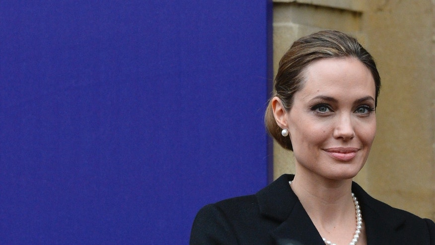 Actress Angelina Jolie poses for a photograph as she arrives for the G8 Foreign Ministers Meeting in central London.
