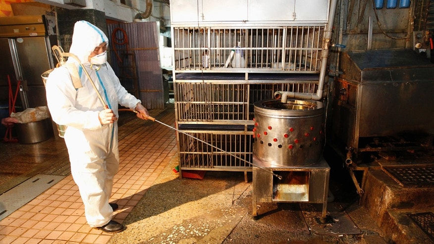 A janitor sprays disinfectant at empty chicken cages in a traditional market in New Taipei city.