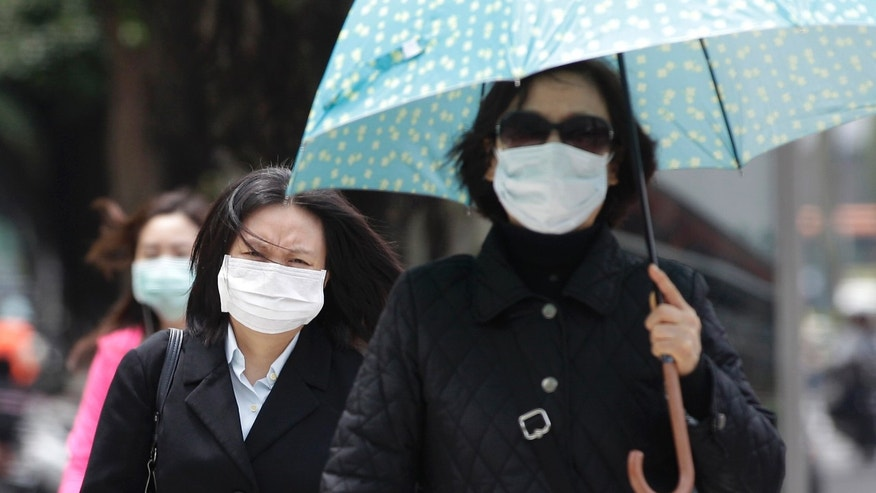 Pedestrians wearing medical masks walk on the street outside National Taiwan University Hospital in Taipei.