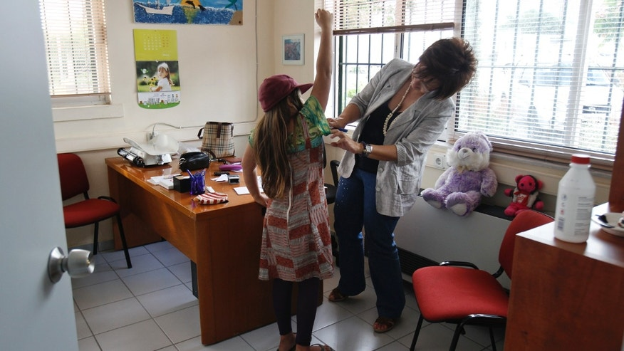 A pediatrician examines a girl inside a social medical center in the Helliniko suburb of Athens.