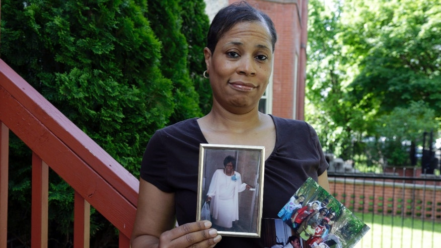 Breast cancer survivor Alicia Cook holds photos of family members who have also been afflicted by breast cancer, outside her home in Chicago. New research shows genetic breast cancer is more common in black women than previously thought. (AP Photo/M. Spencer Green)
