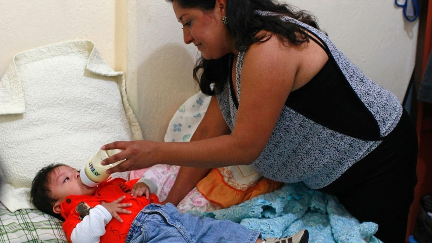 Ruth Gonzalez, a clothing company manager, feeds baby formula to her 9-month-old son Luis Fernando at her home in Mexico City.