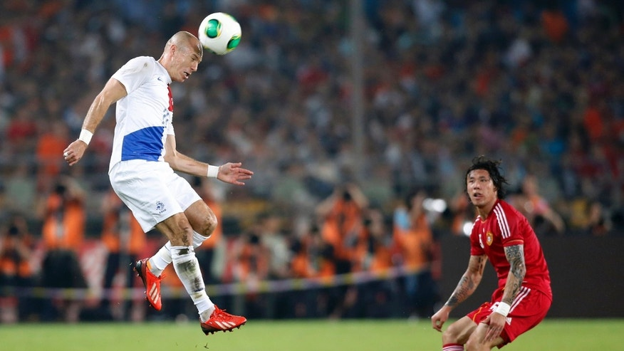Arjen Robben (L) of the Netherlands jumps for the ball as Zhang Linpeng of China looks on during their international friendly soccer match at the Workers' Stadium in Beijing.