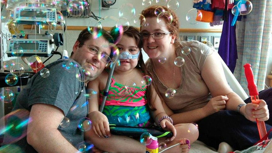 FILE - In this May 30, 2013 file photo provided by the Murnaghan family, Sarah Murnaghan, center, celebrates the 100th day of her stay in Children's Hospital of Philadelphia with her father, Fran, left, and mother, Janet. The 10-year-old suburban Philadelphia girl received a lung transplant there Wednesday, June 12, 2013, her family said. (AP Photo/Murnaghan Family, File)