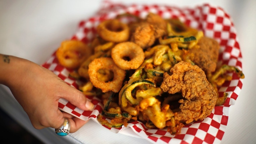 A woman holds a plate of fried food at the Los Angeles County Fair in Pomona, California September 5, 2012. The nation's largest county fair, running from August 31 to September 30, is celebrating its 90th anniversary.  REUTERS/Lucy Nicholson (UNITED STATES - Tags: FOOD SOCIETY ANNIVERSARY) - RTR37K1S