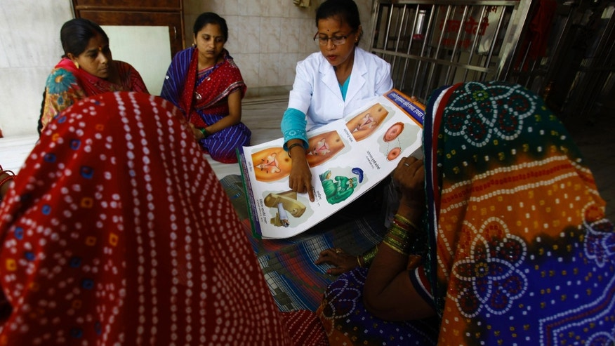 In this Tuesday, May 21, 2013 photo, Anjali S, a health work from Tata Memorial Hospital, briefs a group of women about cervical cancer during one of her regular visit to a slum in Mumbai, India. (AP Photo/Rafiq Maqbool)