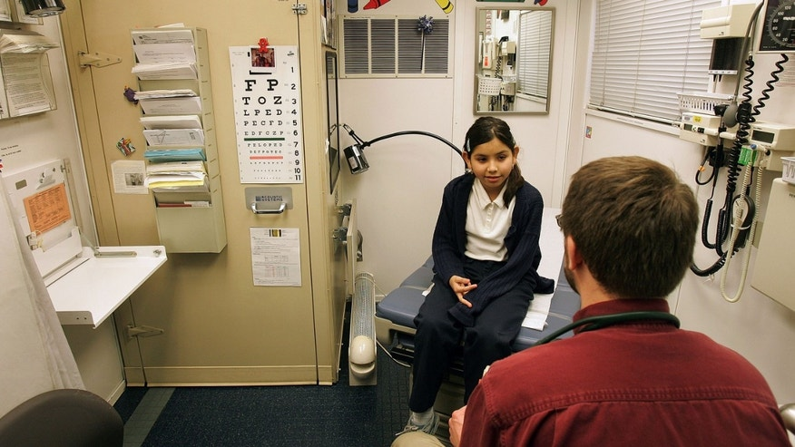 "CICERO, IL - FEBRUARY 22:  Fourth-grader Arylu Paniagua, 9, talks to Dr. Michael Paul after a physical exam in the Loyola Pediatric Mobile Health Unit, parked outside Columbus West Elementary School, February 22, 2005 in Cicero, Illinois. The Loyola Pediatric Mobile Health Unit, the first ""doctor's office on wheels"" in the Midwest which provides free medical care to underserved and uninsured children, reached its 1,500 clinic visit in the community with this stop. The unit, the first if its kind in the world, serves as a national model for other children's hospitals and started traveling in the fall of 1998 with one community partner and now has 350 community partners in the Chicago area.  (Photo by Tim Boyle/Getty Images)"