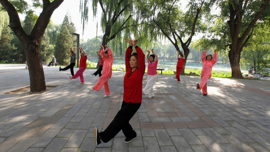 People practise tai chi, a Chinese martial art, during morning exercises at Longtan Park in Beijing.