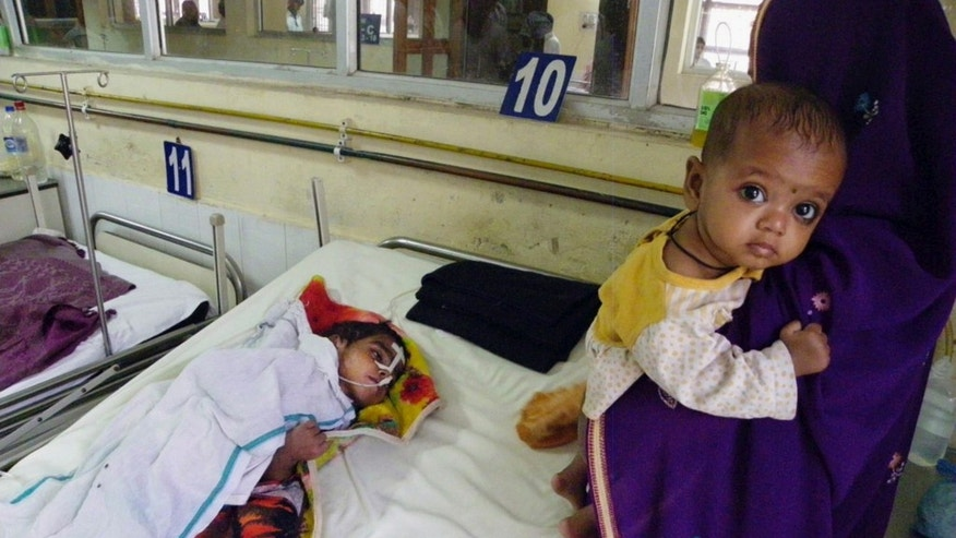 Sangita Devi, right, stands near the bed of her son Anup Kumar, 4, who has been in hospital for the last four months receiving treatment for encephalitis in Gorakhpur in Uttar Pradesh state, India.
