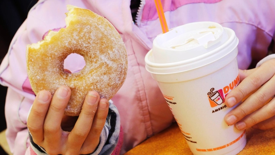 FILE- In this Feb. 14, 2013 file photo, a girl holds a beverage, served in a foam cup, and a donut at a Dunkin' Donuts in New York. A proposal to eliminate plastic foam takeout containers in New York City was met with criticism Wednesday, June 12, 2013, by restaurateurs who said a ban on the ubiquitous containers would drive up costs and potentially put them out of business. (AP Photo/Mark Lennihan, File)