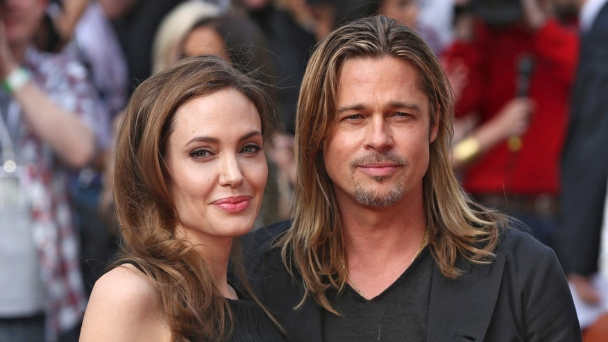 Angelina Jolie poses with Brad Pitt at her first public appearance after announcing she underwent a double mastectomy in February 2013. Jolie tested positive for the BRCA gene.