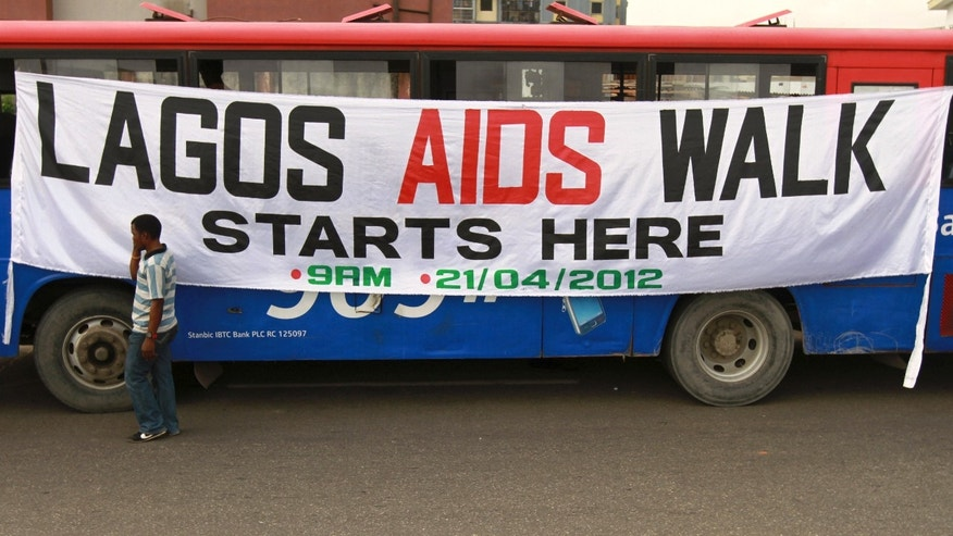 A man walks past a banner tied on a bus before the start of a charity walk on HIV/AIDS at the Ebute Mata district in Nigeria's commercial capital Lagos.