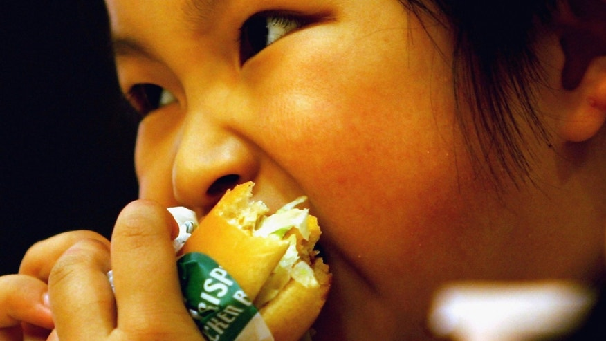 BEIJING - MAY 31: A Chinese girl eats a hamburger at an American fast food chain for an activity to mark International Children's Day with her parents on May 31, 2005 in Beijing, China. The International Children's Day falls on June 1 every year in the mainland. (Photo by Guang Niu/Getty Images)