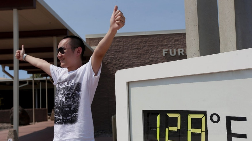 June 28, 2013: Cheng Jia, of china, poses by a digital thermometer at the Furnace Creek Vistitor Center in Death Vally National Park Friday in Furnace Creek, Calif.