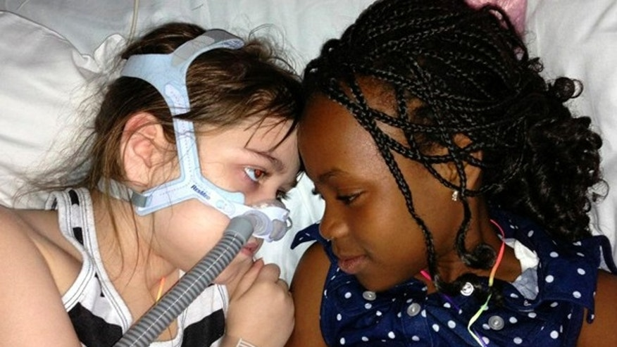 In this May 30, 2013 file photo provided by the Murnaghan family, Sarah Murnaghan, left, lies in her hospital bed next to her sister Ella on the 100th day of her stay in Children's Hospital of Philadelphia.