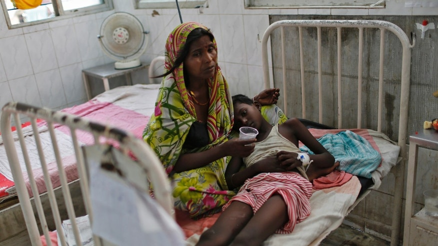 A sick boy lies on his mother's lap inside a hospital after he consumed contaminated meals given to children at a school on Tuesday, in the eastern Indian city of Patna July 18, 2013.